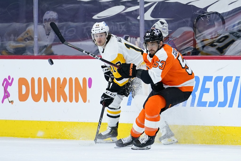 Philadelphia Flyers' Shayne Gostisbehere, right, and Pittsburgh Penguins' Jared McCann battle for the puck during the second period of an NHL hockey g...