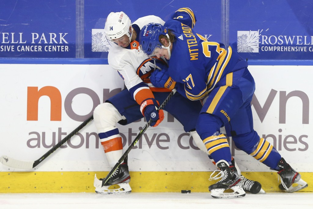 Buffalo Sabres forward Casey Mittelstadt (37) and New York Islanders forward Travis Zajac (14) battle for the puck during the second period of an NHL ...