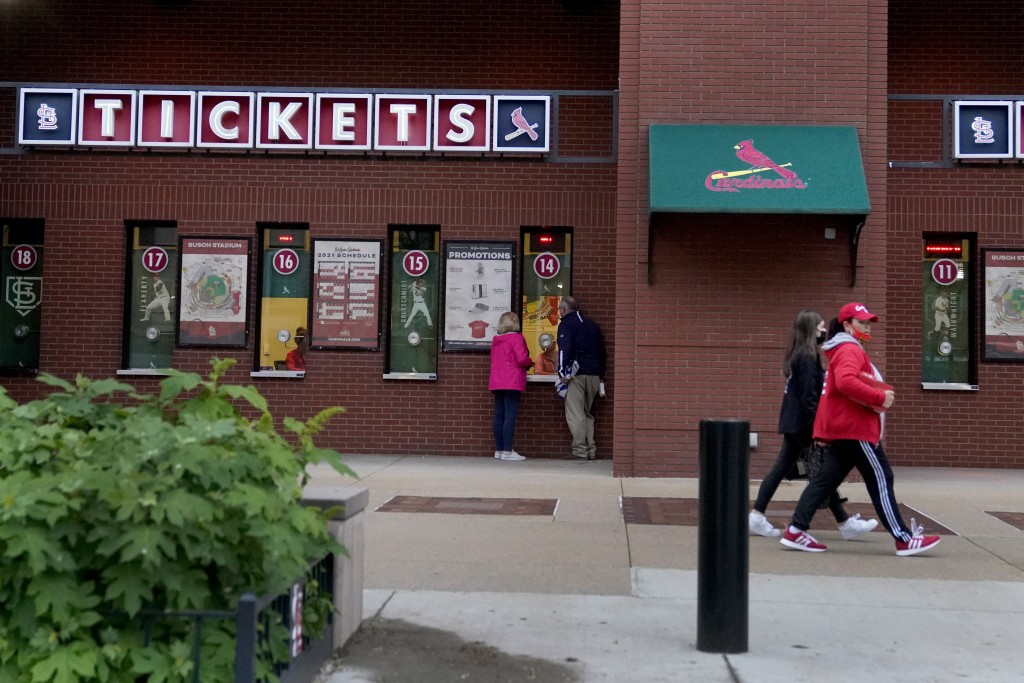 People walk outside Busch Stadium after the start of a baseball game between the St. Louis Cardinals and the New York Mets was delayed because of rain...