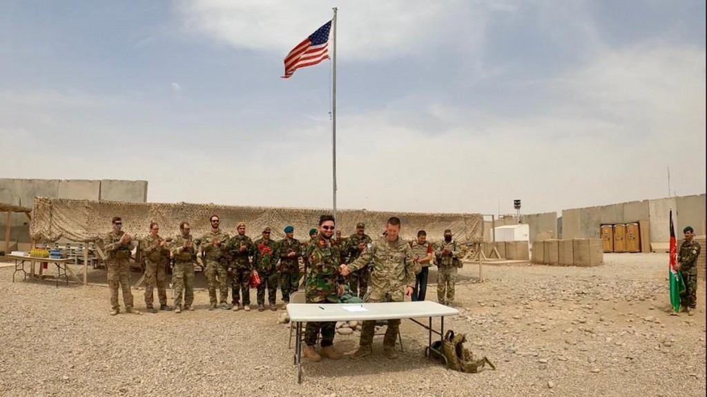 A U.S. flag flies as American and Afghan soldiers attend a handover ceremony from the U.S. Army to the Afghan National Army, at Camp Anthonic, in Helm...