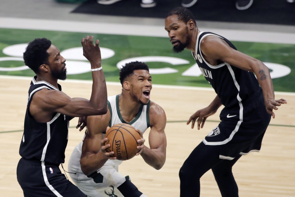 Milwaukee Bucks' Giannis Antetokounmpo, middle, drives to the basket between Brooklyn Nets' Jeff Green, left, and Kevin Durant, right, during the firs...