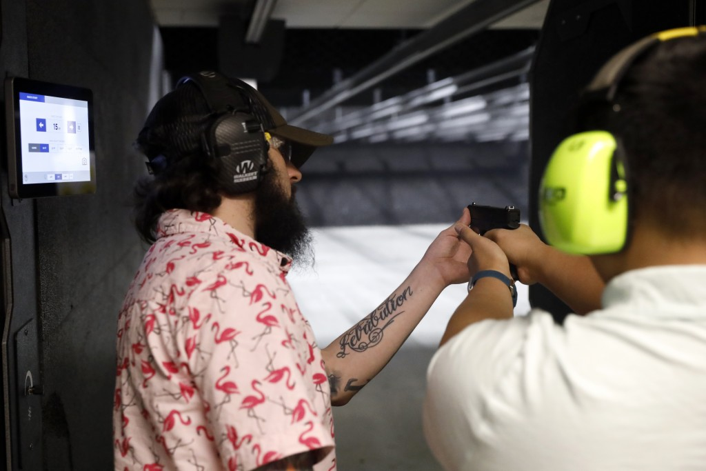 Firearms trainer Kevin Burke, left, instructs new gun owner Troy Deguzman during a shooting session at Maxon Shooter's Supplies and Indoor Range, Frid...