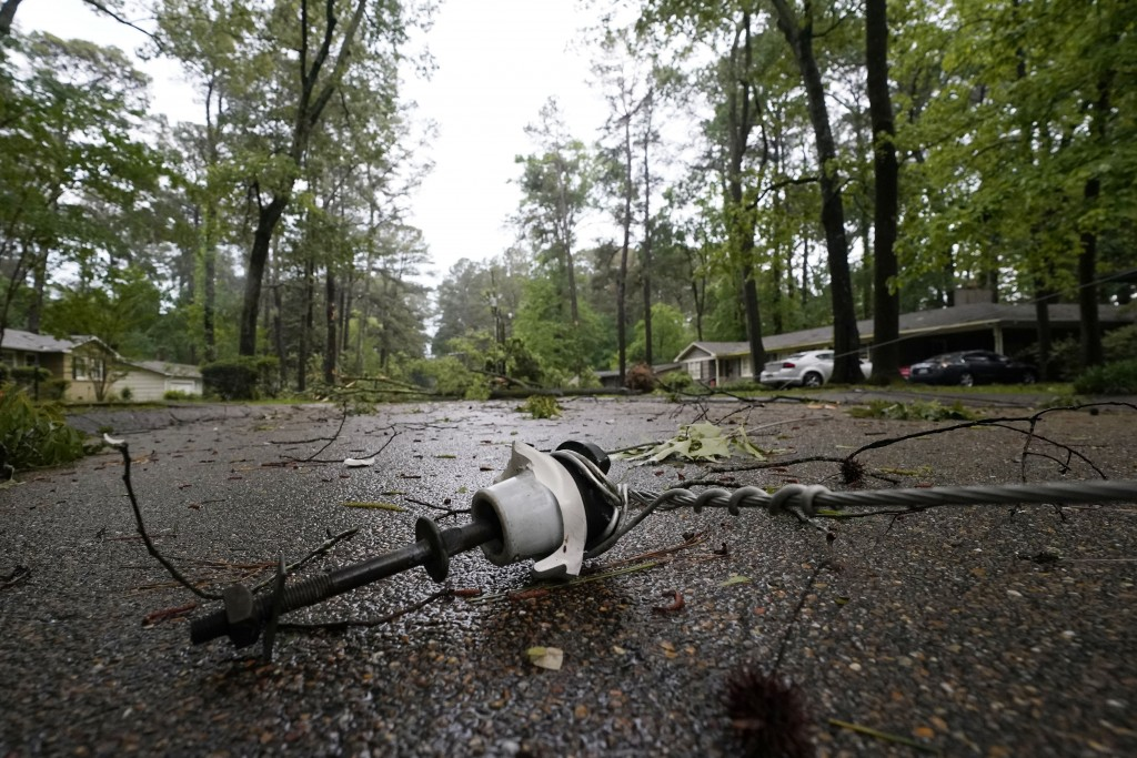 This downed utility line from a fallen tree in a northeast Jackson, Miss., neighborhood, was not an unfamiliar sight following a bout of high winds an...