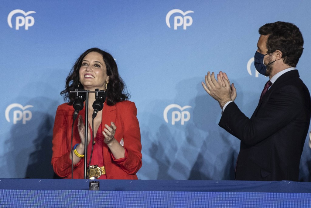 Conservative Madrid regional president Isabel Diaz Ayuso, left, and Popular party leader Pablo Casasdo celebrate election results outside the popular ...