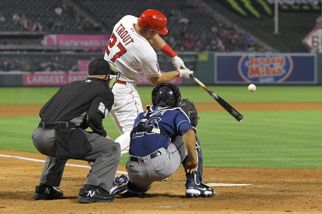 Los Angeles Angels' Mike Trout, center, hits a solo home run as Tampa Bay Rays catcher Francisco Mejia, right, and home plate umpire Sean Barber watch...