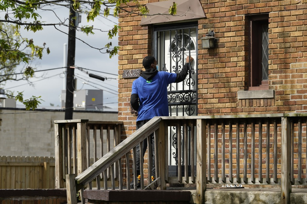 Sirgregory Allen knocks on a door before leaving a flyer on a home in Detroit, Tuesday, May 4, 2021. Officials are walking door-to-door to encourage r...
