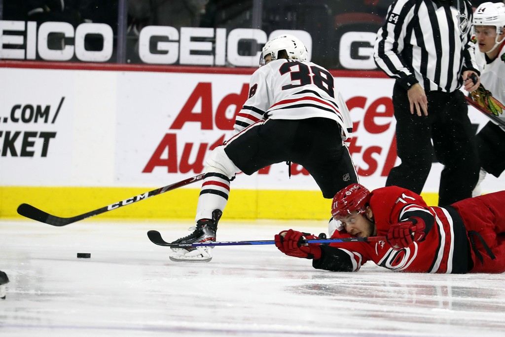 Carolina Hurricanes' Jesper Fast (71) collides with Chicago Blackhawks' Brandon Hagel (38) and loses control of the puck during the first period of an...