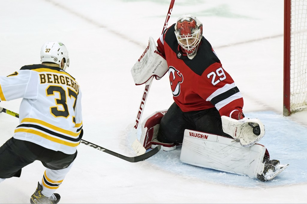 New Jersey Devils goaltender Mackenzie Blackwood (29) makes a glove save with Boston Bruins center Patrice Bergeron (37) threatening in front of the c...