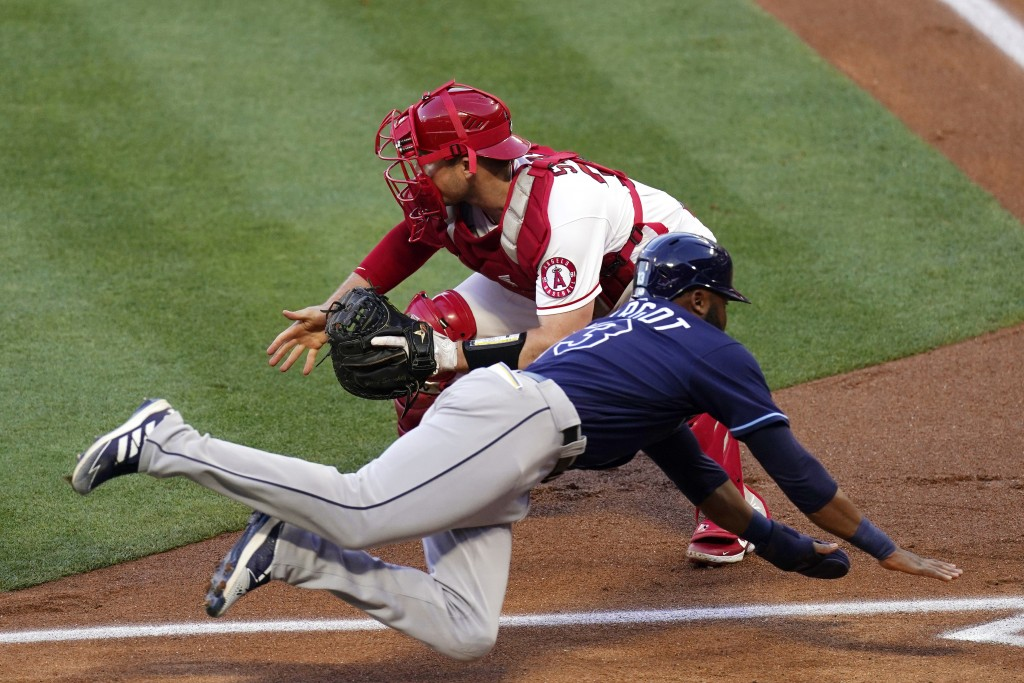 Tampa Bay Rays' Manuel Margot, below, scores after a single by Brandon Lowe and a fielding error by Los Angeles Angels second baseman David Fletcher a...