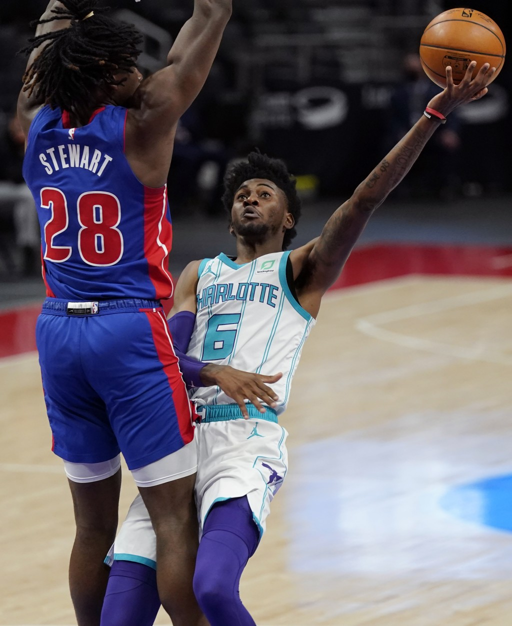 Charlotte Hornets forward Jalen McDaniels (6) is defended by Detroit Pistons center Isaiah Stewart (28) during the first half of an NBA basketball gam...