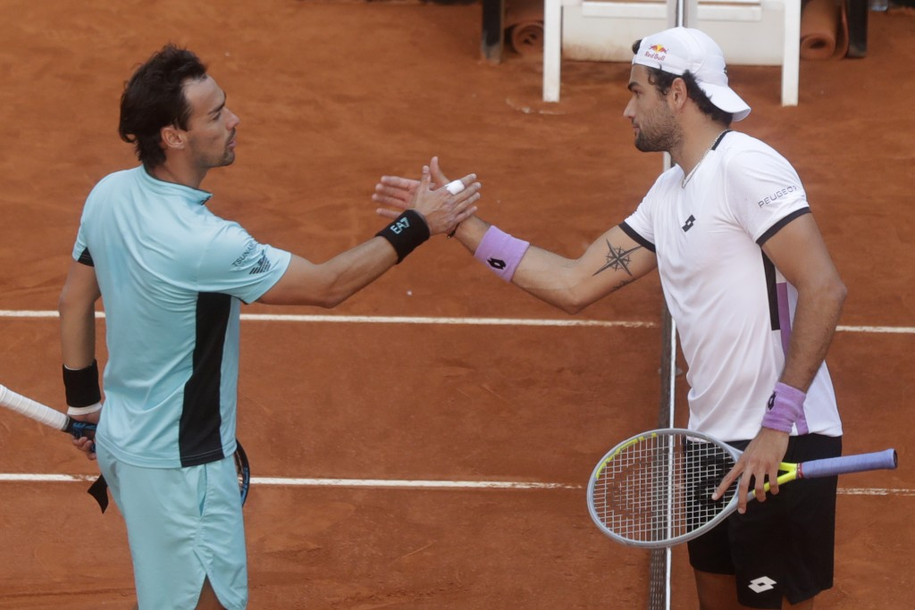 Matteo Berrettini of Italy, right, shakes hands with Fabio Fognini of Italy at the end of their match at the Madrid Open tennis tournament in Madrid, ...