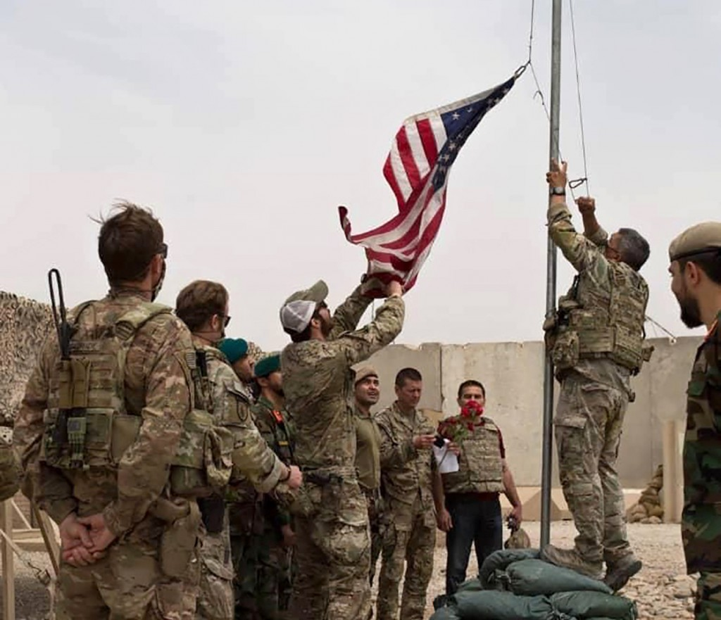 A U.S. flag is lowered as American and Afghan soldiers attend a handover ceremony from the U.S. Army to the Afghan National Army, at Camp Anthonic, in...