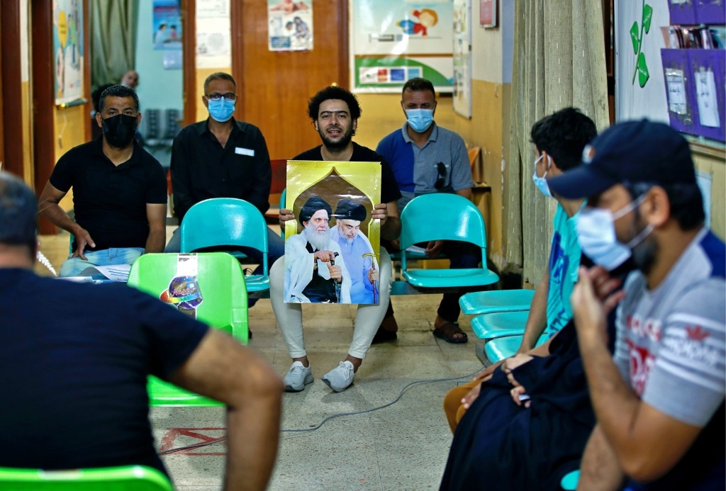 A follower of populist Shiite cleric Muqtada al-Sadr holds a picture of him while waiting with others to receive a dose of the Chinese Sinopharm coron...