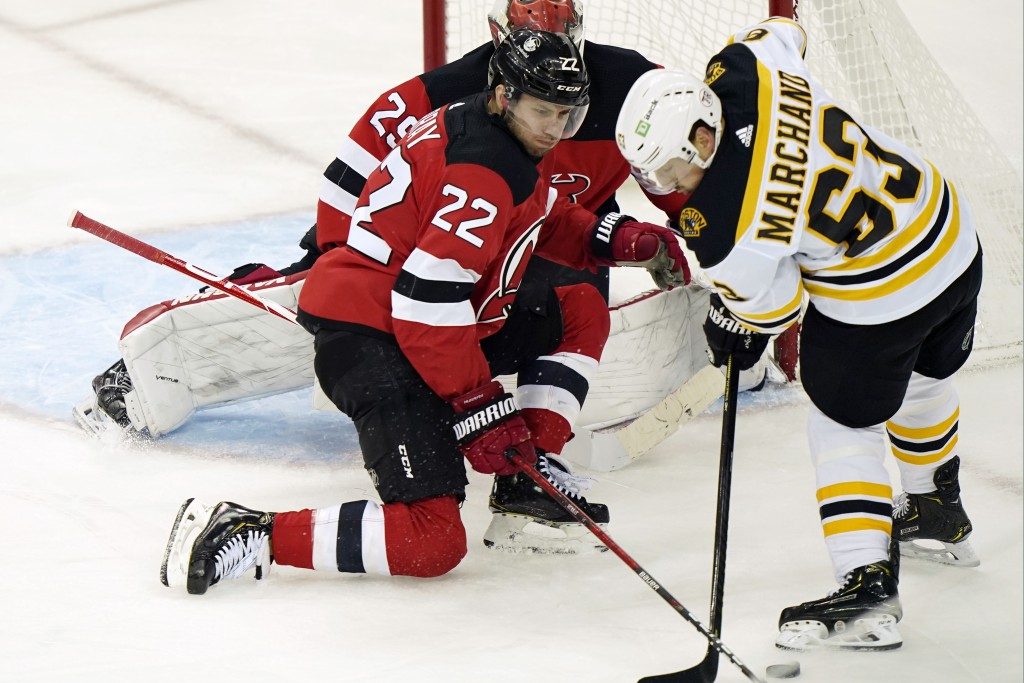 New Jersey Devils defenseman Ryan Murray (22) tries to keep Boston Bruins left wing Brad Marchand (63) from the puck in front of Devils goaltender Mac...