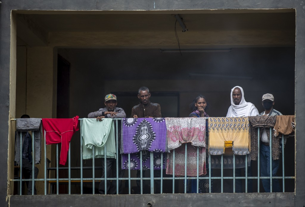 """Displaced Tigrayans look out from a balcony next to washed clothes as women prepare """"Injera"""" flatbread in a courtyard below, at the Hadnet General Sec..."""
