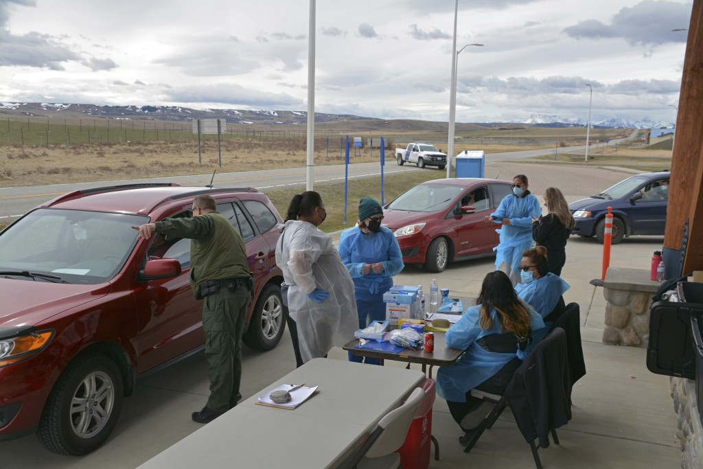 In this Thursday, April 29, 2021, photo, a U.S. Border Patrol agent directs a driver after the passenger received a COVID-19 vaccine from nurses of th...