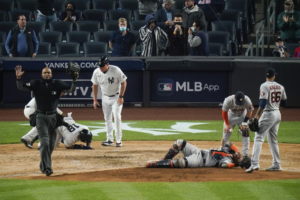 Players gather around New York Yankees' Rougned Odor (18) and Houston Astros catcher Martin Maldonado after they were injured during the sixth inning ...