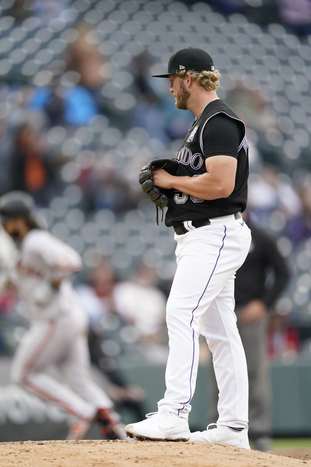 Colorado Rockies relief pitcher Lucas Gilbreath, front, looks on as San Francisco Giants' Brandon Crawford circles the bases after hitting a two-run h...