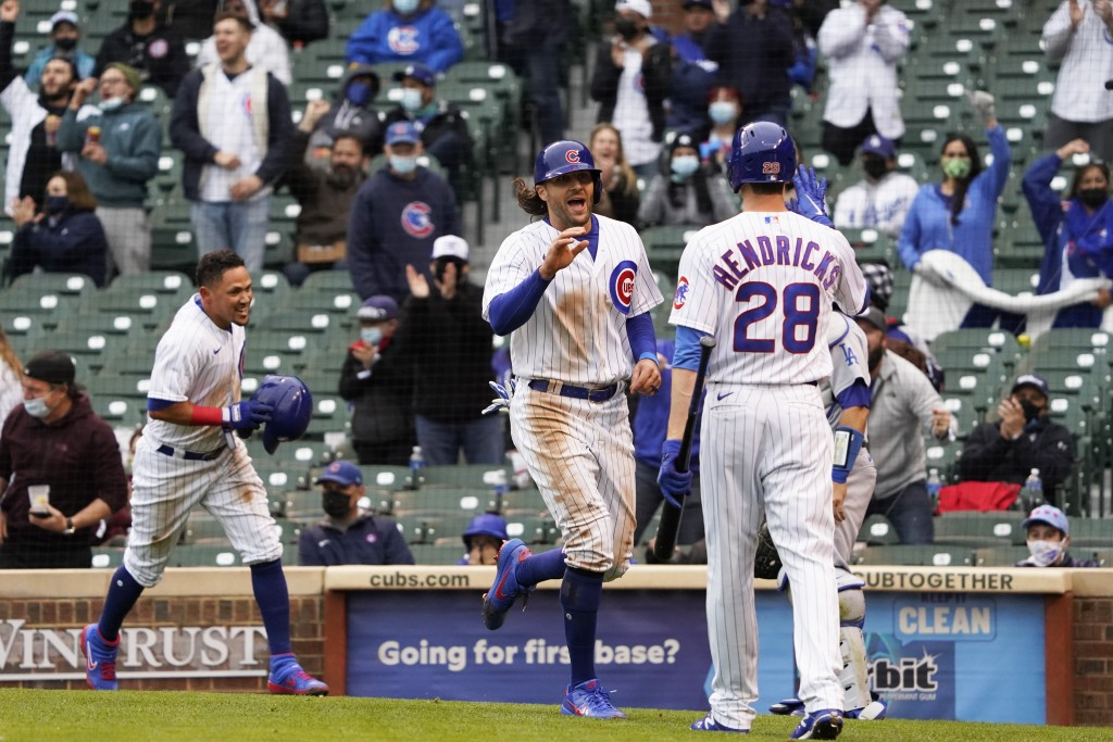 Chicago Cubs' Ildemaro Vargas, left and Jake Marisnick, center, celebrate after scoring on a wild pitch against the Los Angeles Dodgers as Kyle Hendri...