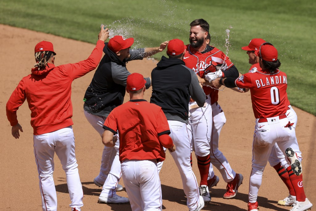 Cincinnati Reds' Jesse Winker, back right, celebrates with teammates after hitting an RBI walk-off single during the tenth inning of a baseball game a...