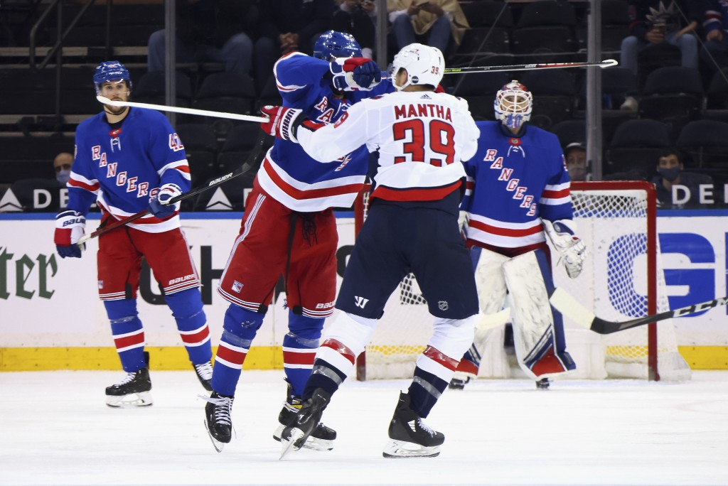 New York Rangers' Pavel Buchnevich (89) hits Washington Capitals' Anthony Mantha (39) with his stick during the second period of an NHL hockey game We...