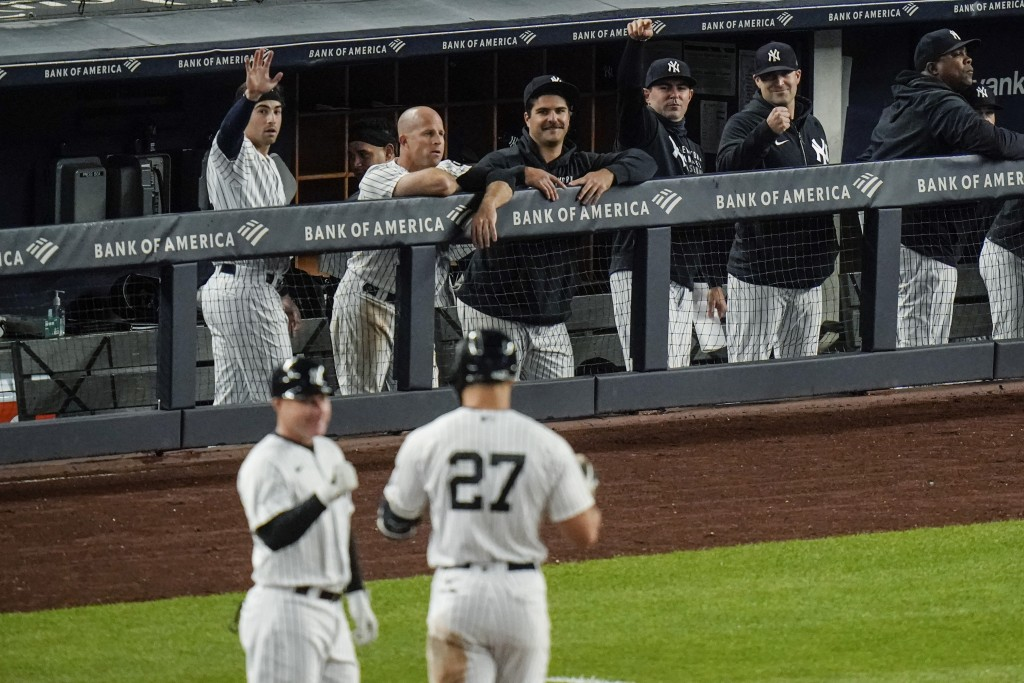 New York Yankees players gesture to Giancarlo Stanton (27) after stanton drove in a run with a single during the eighth inning of a baseball game agai...