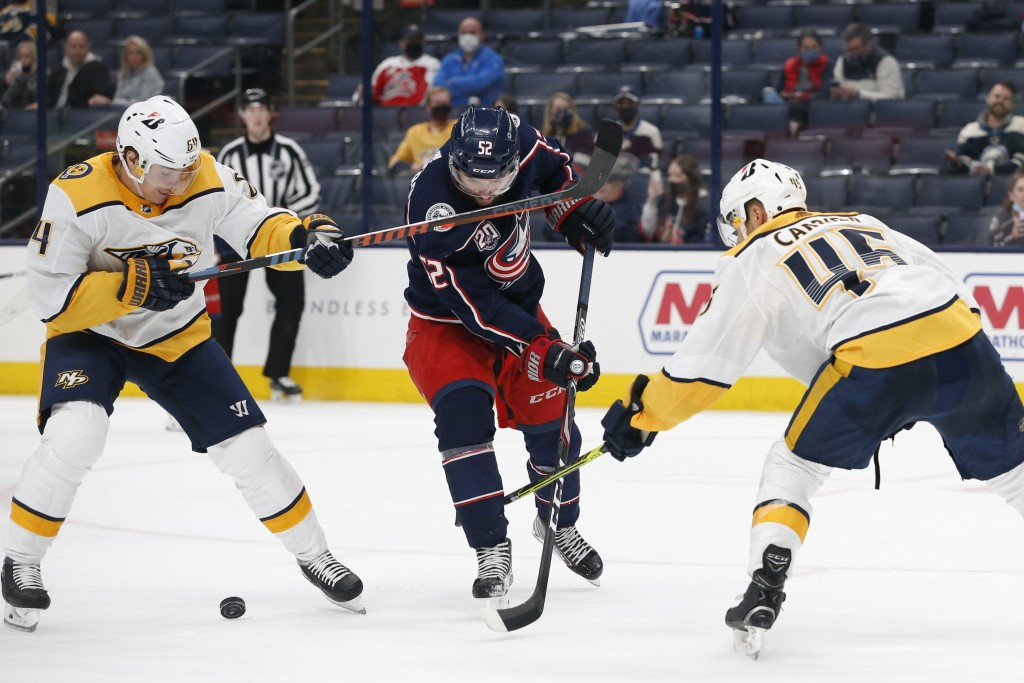 Columbus Blue Jackets' Emil Bemstrom, center, tries to shoot the puck between Nashville Predators' Mikael Granlund, left, and Alexandre Carrier during...
