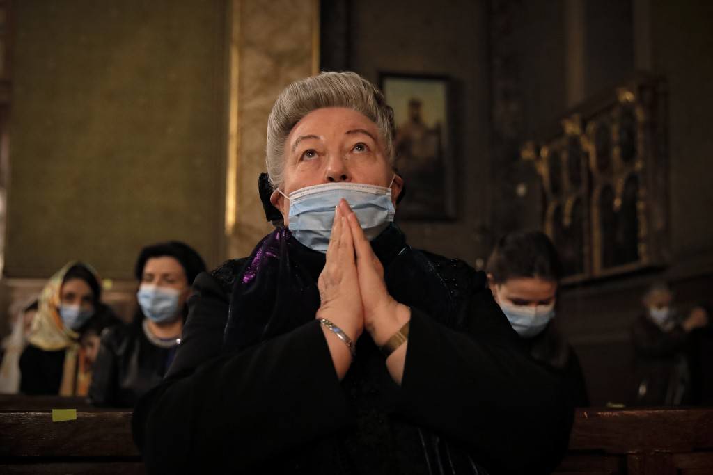A woman of the Armenian community in Romania, wearing face mask, prays during the Easter religious service, at the Armenian Church in Bucharest, Roman...