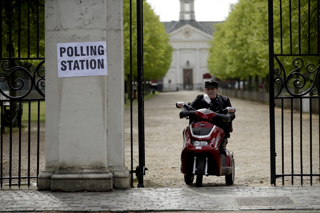 A Chelsea Pensioner drives his mobility scooter past a sign for a polling station after voting in London, Thursday, May 6, 2021. Millions of people ac...