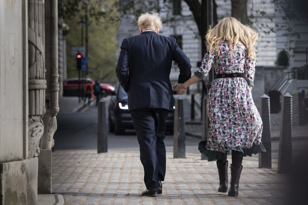 Britain's Prime Minister Boris Johnson and his fiancee Carrie Symonds leave after casting their vote in the local and London Mayoral election, at Meth...