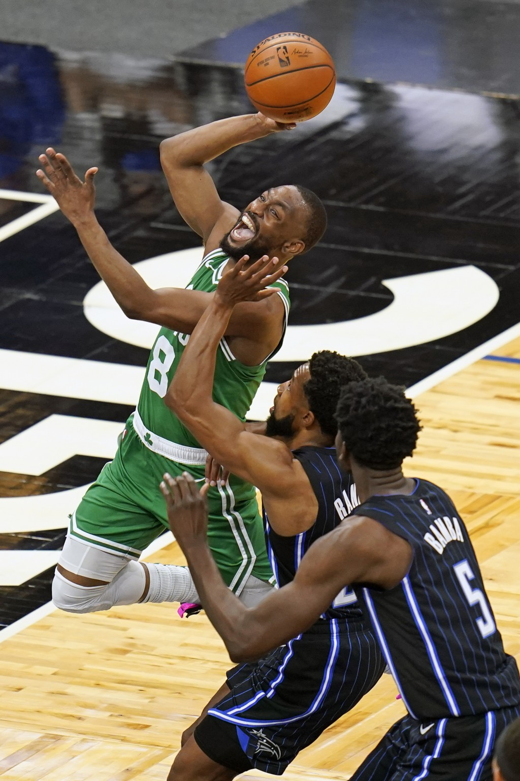 Boston Celtics guard Kemba Walker (8) goes to the basket for a shot past Orlando Magic guard Chasson Randle, center, and center Mo Bamba (5) during th...
