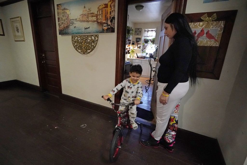 FILE - In this March 10, 2021, file photo, Isabel Miranda's 4-year-old son, Julian, rides his bike into the hallway of their rental apartment in Haver...