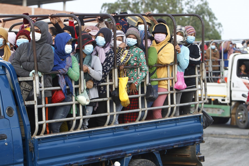 Garment workers stand on the trucks as they head to work outside Phnom Penh, Cambodia, Thursday, May 6, 2021. Cambodia on Thursday ended a lockdown in...