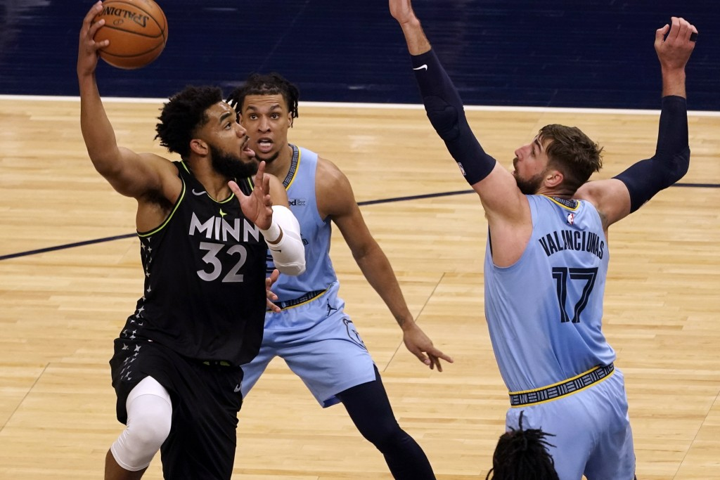 Minnesota Timberwolves' Karl-Anthony Towns (32) shoots as Memphis Grizzlies' Jonas Valanciunas (17) defends in the first half of an NBA basketball gam...