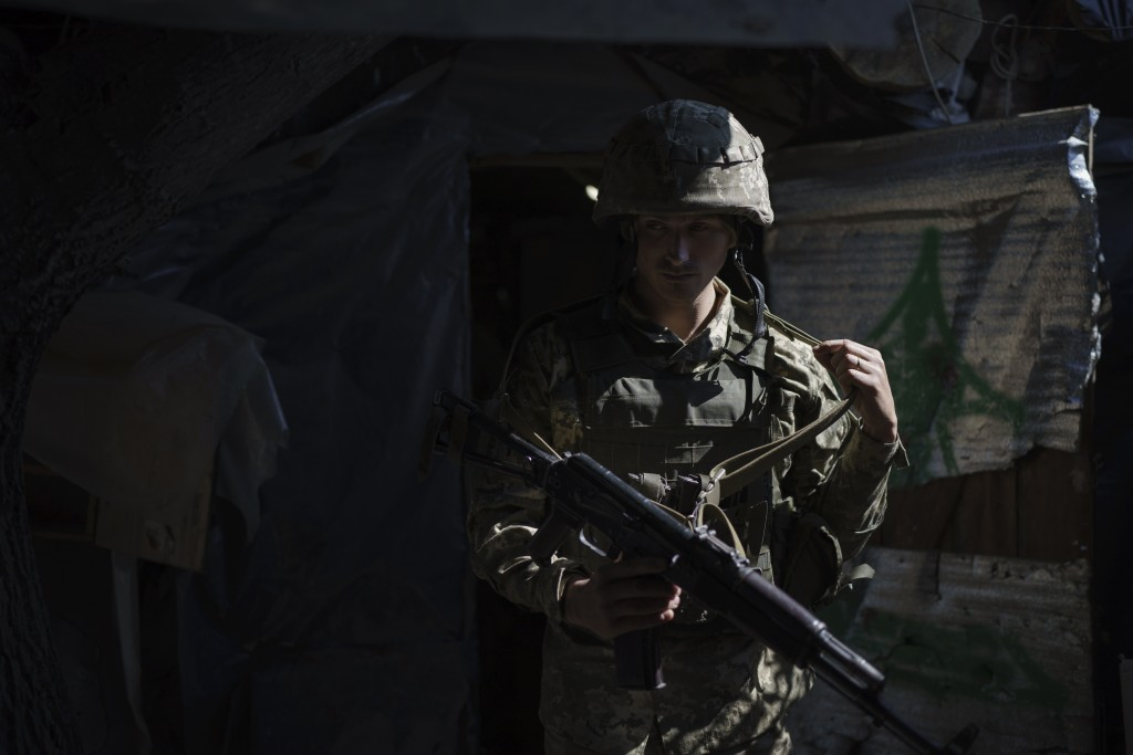 FILE - In this Wednesday, May 5, 2021 file photo, a Ukrainian soldier adjusts his rifle sling as he leaves his position on the line of separation from...