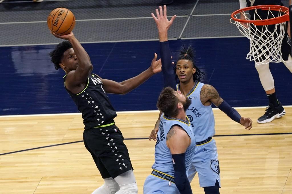 Minnesota Timberwolves' Anthony Edwards, left, shoots over Memphis Grizzlies' Jonas Valanciunas, center, during the first half of an NBA basketball ga...
