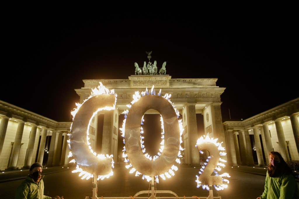 Activists of the environment organization Greenpeace protest with CO2 letters illuminated with flames in front of the Brandenburg Gate against the cli...