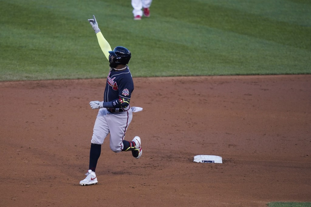 Atlanta Braves' Marcell Ozuna celebrates as he runs the bases on a grand slam during the third inning of the team's baseball game against the Washingt...