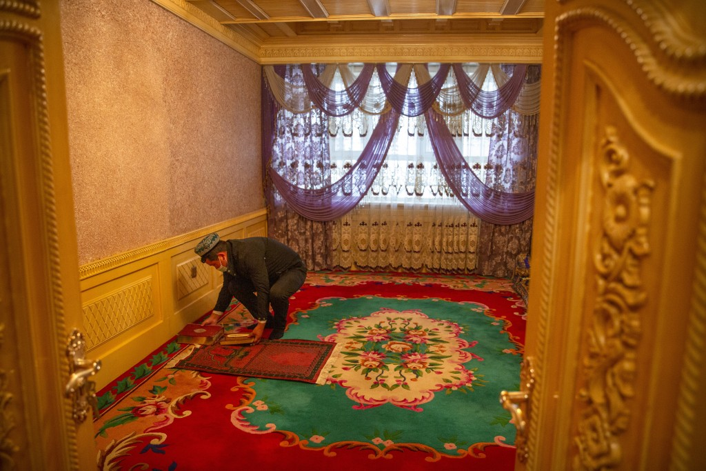 Tursunjan Mamat sets down a copy of the Quran during a government organized visit for foreign journalists to his home in Aksu in western China's Xinji...