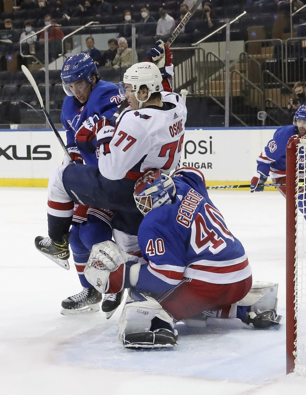 New York Rangers' Libor Hajek (25) and Alexandar Georgiev (40) defend against Washington Capitals' T.J. Oshie (77) during the second period of an NHL ...