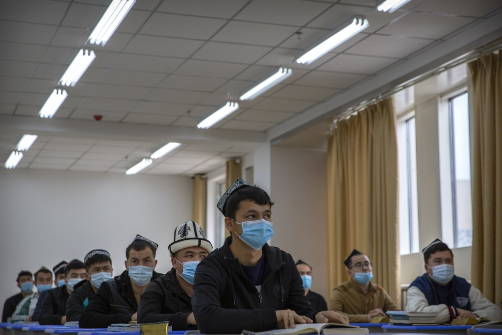 Uyghurs and other students listen to an instructor during a class at the Xinjiang Islamic Institute, as seen during a government organized visit for f...