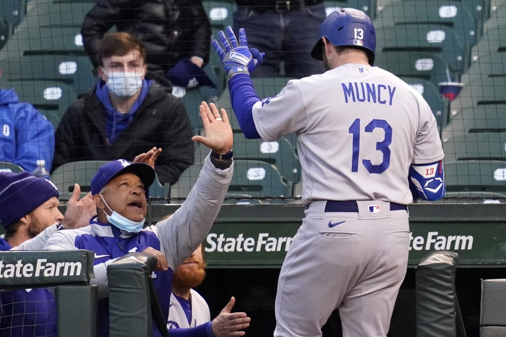 Los Angeles Dodgers manager Dave Roberts, left, congratulates Max Muncy after his solo home run during the fourth inning of a baseball game against th...