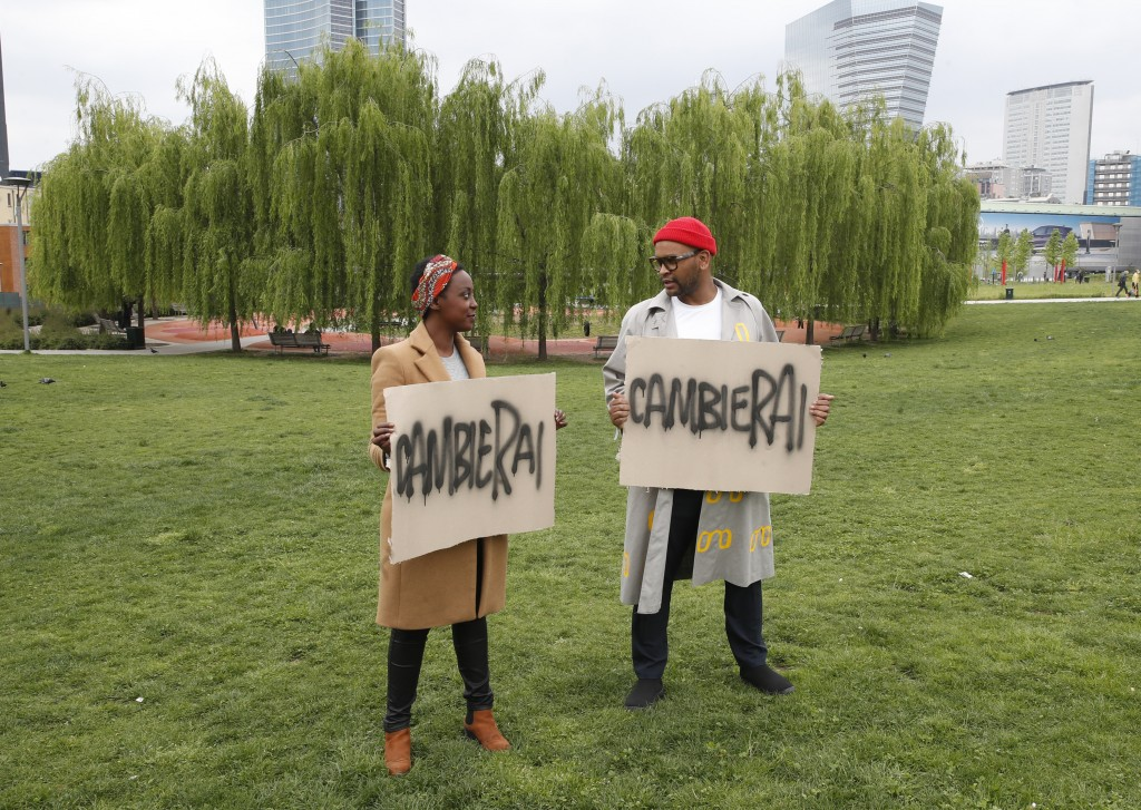 """Sara Lemlem, left, and Jermay Gabriel Michael pose with banners reading in Italian """"you will change"""" before an interview with the Associated Press, in..."""
