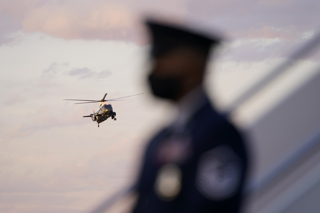 FILE - In this Feb. 5, 2021, file photo Marine One, with President Joe Biden aboard, is seen past a member of the U.S. Air Force as it approaches Andr...
