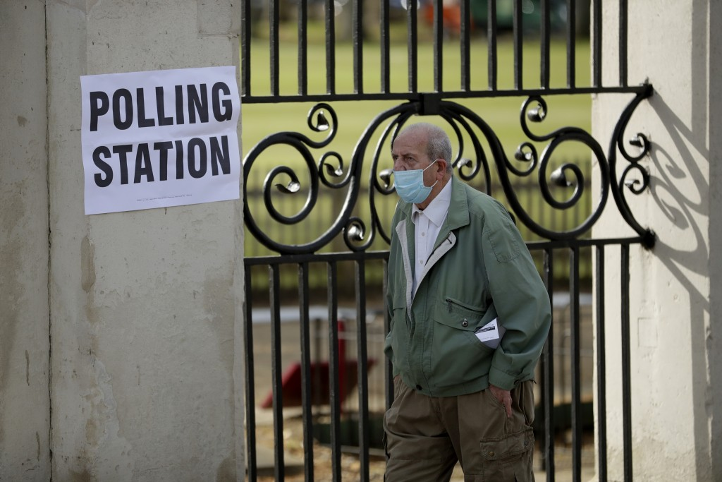 A men wearing a surgical mask to curb the spread of coronavirus walks past a sign for a polling station as he arrives to vote in London, Thursday, May...