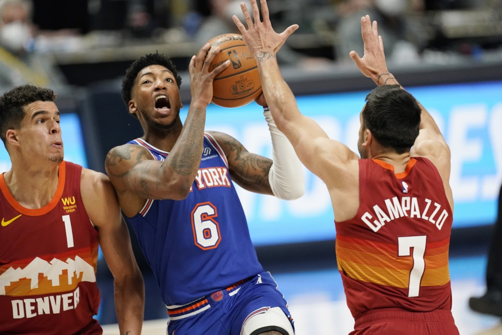 New York Knicks guard Elfrid Payton (6) drives to the rim between Denver Nuggets forward Michael Porter Jr. (1) and guard Facundo Campazzo (7) in the ...