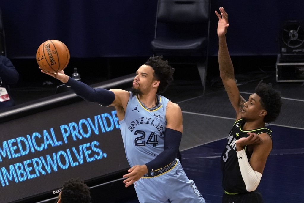 Memphis Grizzlies' Dillon Brooks (24) shoots past Minnesota Timberwolves' Jaden McDaniels (3) during the first half of an NBA basketball game Wednesda...