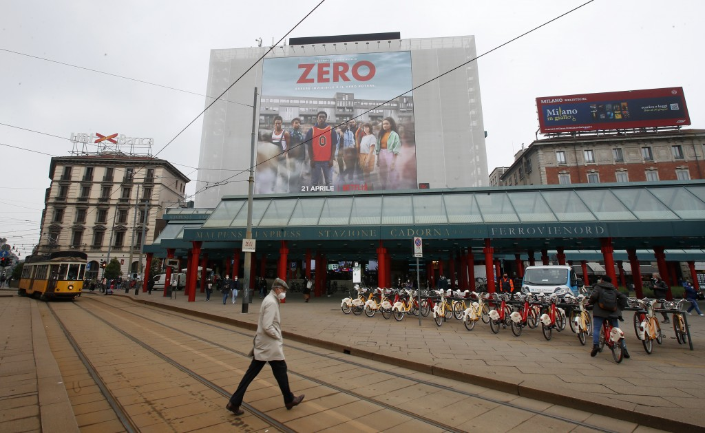"""A man walks under a poster advertising the TV Series """"Zero"""", at Cadorna square in Milan, Italy, Tuesday, April 27, 2021. The Netflix series """"Zero,"""" wh..."""