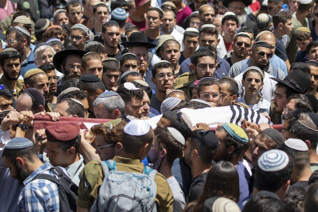 Family and friends of Yehuda Guetta carry his covered body during his funeral service in Jerusalem, Thursday, May 6, 2021. Guetta, 19, wounded in a dr...