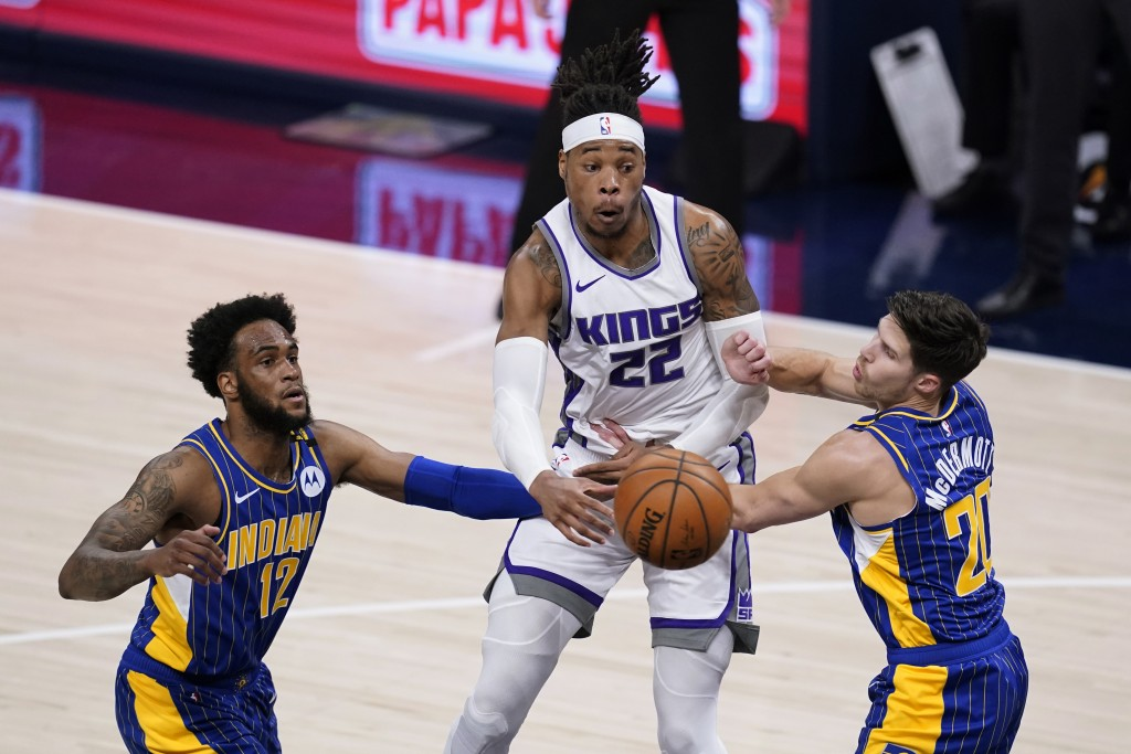 Sacramento Kings' Richaun Holmes (22) passes the ball between Indiana Pacers' Oshae Brissett (12) and Doug McDermott (20) during the first half of an ...